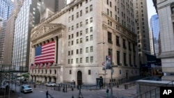 A giant American Flag hangs on the New York Stock Exchange, Sept. 21, 2020. Stocks fell on Wall Street, joining a global tumble for markets.