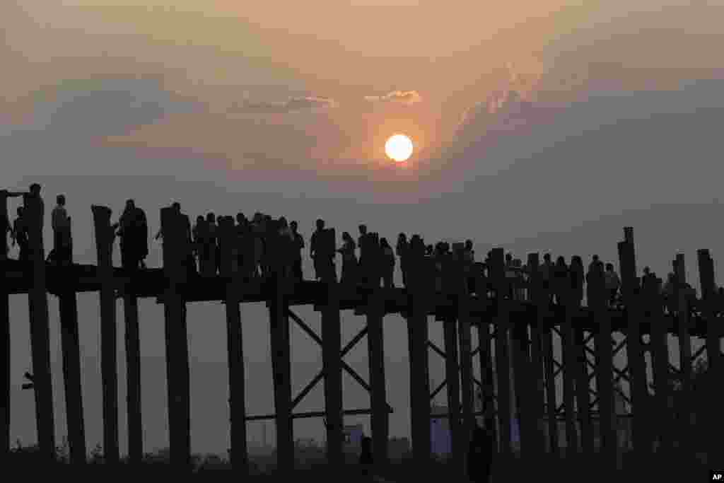 អ្នកដំណើរក្នុងស្រុកនិងបរទេសដើរកាត់ព្រះអាទិត្យលិចនៅលើស្ពាន U Bein Bridge ស្ពានឈើដ៏វែងជាងគេដែលភ្ជាប់ច្រាំងពីរនៃបឹង Taungthaman ក្នុងទីក្រុង Mandalay ប្រទេសមីយ៉ាន់ម៉ាកាលពីថ្ងៃទី០៣ មេសា ២០១៨។