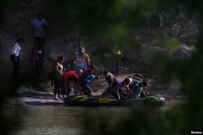 미국과 국경을 접하는 멕시코 리오그란데에서 남자, 여자, 아이들이 불법으로 국경을 넘기 위해 뗏목에 오르고 있다.