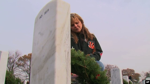 Ilka Halliday places a Christmas wreath at the grave of her son, Christopher Wilson, at Arlington National Cemetery