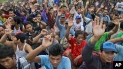 Trong bức ảnh chụp ngày 3 tháng 4 năm 2015, các ngư dân Miến Điện được giải cứu giơ tay khi được hỏi ai trong số họ muốn trở về nhà tại công ty đánh bắt cá Tài nguyên Pusaka Benjina, quần đảo Aru, Indonesia.