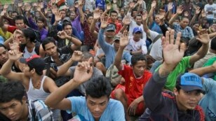 FILE - In this April 3, 2015 photo, rescued Burmese fishermen raise their hands as they are asked who among them wants to go home at the compound of Pusaka Benjina Resources fishing company in Benjina, Aru Islands, Indonesia. Two Indonesians and five Thai were arrested on charges of human trafficking connected with slavery in the seafood industry, Indonesian police said on May 12.