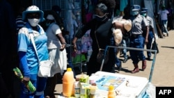 FILE: Spiwe Tembo, an informal trader who makes her living selling buns is handcuffed to another vendor after their arrest by police at a busy shopping complex alongside a commuter bus rank in Harare, April 15 2021.