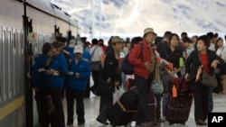 Tourists file out of a passenger train that arrived at the train station in Lhasa, southwestern China's Tibet province, Tuesday, July 31, 2007. Built at a cost of US$4.2 billion, the Chinese government says the railway linking Tibet to the rest of China is projected to help double tourism revenues in Tibet by 2010, and cut transportation costs for goods by 75 percent. (AP Photo/Ng Han Guan)