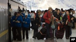 Tourists file out of a passenger train that arrived at the train station in Lhasa