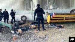 Policías federales cerca de los cadáveres de los supuestos narcotraficantes en el Rancho del Sol, en Michoacán.