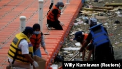Anggota kelompok lingkungan Bank Sampah Sungai Cisadane (Banksa Suci) mengumpulkan sampah medis di Sungai Cisadane di Tangerang, Provinsi Banten, 2 Agustus 2020. (Foto: Reuters/Willy Kurniawan)