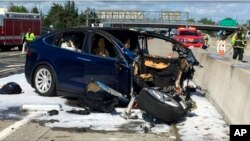 FILE - Photo provided by KTVU shows emergency personnel working at the scene where a Tesla electric SUV crashed into a barrier on U.S. Highway 101 in Mountain View, Calif., March 23, 2018.