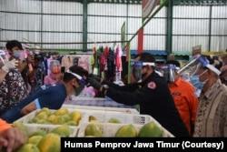 Sekdaprov Jawa Timur memakaikan pelindung wajah kepada para pedagang dan pengunjung Pasar Oro-oro Dowo Malang, Selasa, 21 Juli 2020. (Foto: Humas Pemprov Jawa Timur).