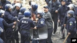 Riot policemen detain a protester during a demonstration in Oued Koriche, Algiers, March 23, 2011