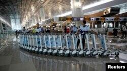 Petugas memindahkan serangkaian troli di Terminal 3 Bandara Soekarno-Hatta pada hari pertama pembukaan terminal tersebut (9/8). (Reuters/Darren Whiteside)