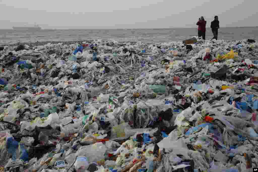 A man takes photos of piles of garbage washed ashore after a storm battered the Mediterranean country at the Zouq Mosbeh costal town, north of Beirut, Lebanon, Jan. 22, 2018.