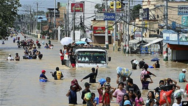 Residents wade through the floodwaters as they evacuate to safer grounds following massive flooding in Calumpit township, Bulacan province, north of Manila, Philippines, September 30, 2011.