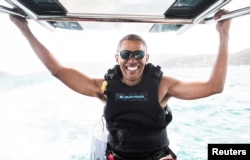 Former U.S. President Barack Obama sits on a boat during a kite surfing outing with British businessman Richard Branson during his holiday on Branson's Moskito island, in the British Virgin Islands, in a picture handed out by Virgin, Feb, 7, 2017.