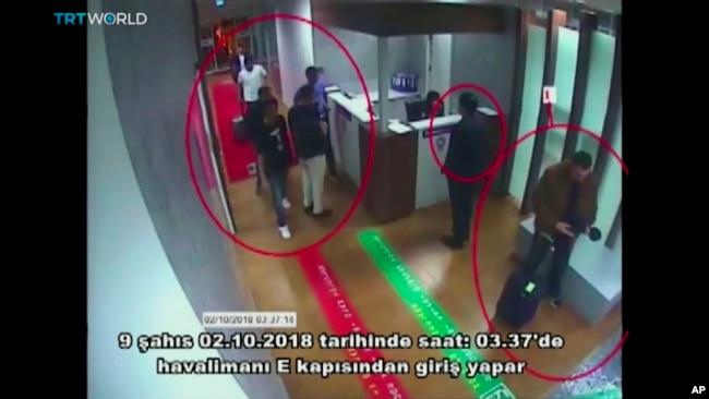 """Esta foto tomada de una cámara de vigilancia muestra una imagen de personas en el aeropuerto internacional Ataturk, en Estambul, Turquía, el 2 de octubre de 2018. El texto en turco, en la pantalla, dice """"nueve personas ingresan por puerta E del aeropuerto. Oct. 2, 2018"""