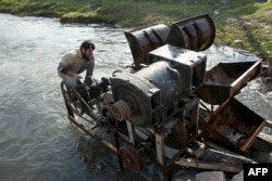 A Syrian man installs a homemade hydroelectric generator, assembled by 43-year-old Abu Saleh, in the Queiq river in the rebel held Bustan al-Qasr district in the east of the northern Syrian city of Aleppo, Nov. 26, 2015.