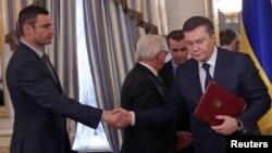 Tinchlik sulhi tuzilishi ortidan Ukraina prezidenti Viktor Yanukovich (o'ngda) muxolifat yetakchilaridan biri Vitaliy Klichko bilan qo'l siqib ko'rishmoqda, 21-fevral, 2014-yil.
