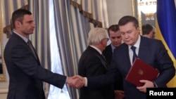 2月21日烏克蘭總統亞努科維奇(右)在簽署歐盟斡旋的和平協議後與反政府領導人握手