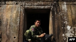 Binh sĩ Campuchia ngồi đánh giày tại ngôi đền Preah Vihear, ngày 8/2/2011. Hồi năm 1962, Tòa án Tư pháp Quốc tế đã ra phán quyết rằng ngôi đền thuộc về Campuchia, nhưng tuyến đường chính dẫn tới ngôi đền lại nằm ở phía Thái Lan