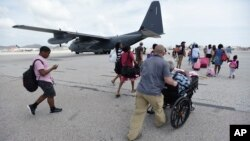 U.S. Air force personnel evacuate residents from Princes Juliana International Airport after the passage of Hurricane Irma, in St. Martin, Sept. 12, 2017. Irma cut a path of devastation across the northern Caribbean, leaving thousands homeless after destroying buildings and uprooting trees.
