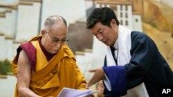 Lobsang Sangay, PM Pemerintah Tibet di pengasingan (kanan) menyerahkan dokumen kepada pemimpin spiritual Tibet, Dalai Lama di Sekolah Pedesaan Anak-anak di wilayah Dharmsala, India (5/6).