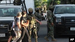 Two women walk next to members of Mexican Navy in Boca del Rio, Veracruz State. Another 32 bodies have been found in three homes in Mexico's eastern state of Veracruz, where dozens of corpses were dumped on a road in broad daylight last month, the navy sa