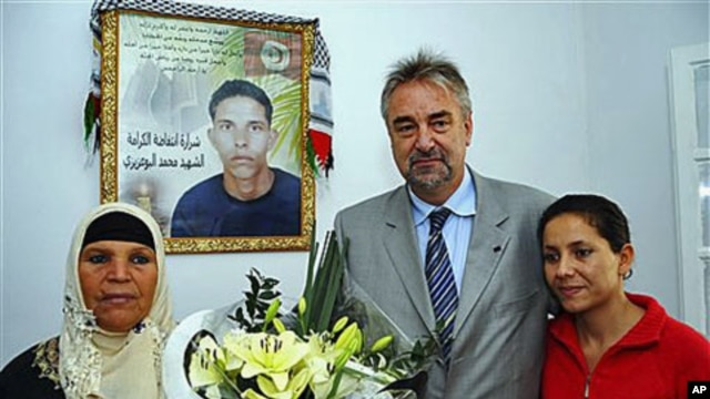 European Union representative Adrianus Koetsenruijter (C) poses with Manoubia Bouazizi (L), mother of Mohamed Bouazizi, a 26-year-old who set himself alight on Dec. 17, 2010 - he is seen on a poster behind - and Leila, sister of Mohamed, outside Tunis, No