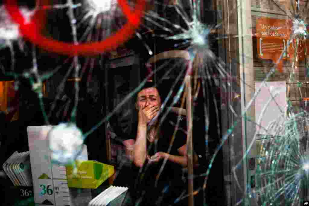 Mireia Arnau menangisi kerusakan tokonya oleh para demonstran selama bentrokan di Barcelona dalam protes mengenai reformasi buruh Spanyol (29/3).