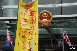 網絡群組元旦遊行到中聯辦門外,高舉港英旗幟及大型符咒,呼籲中聯辦遵守基本法22條,停止干預香港內部事務