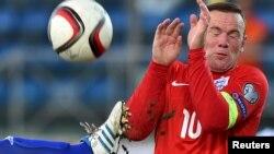 Wayne Rooney (à droite) tente de se couvrir après une parade lors du match de qualification de l'Euro 2016 (football) contre Saint-Marin au stade olympique de Serravalle, Saint-Marin, 5 Septembre2015.