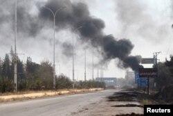 Smoke rises near a damaged road in Dahiyet al-Assad, west Aleppo city, Syria, Oct. 30, 2016.