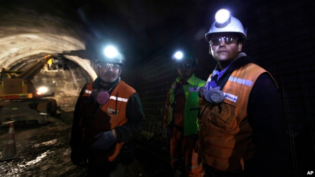 FILE - Foreman Jorge Villanueva, left, and supervisor Omar Rosales, right, look toward the entrance of a tunnel drilled under the Chuquicamata copper mine in the Atacama desert in northern Chile, Sept. 25, 2012.