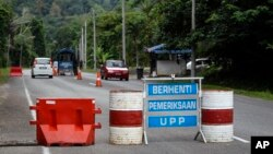 A check point is seen at the entry point to Malaysia - Thailand border in Wang Kelian, Malaysia on Sunday, May 24, 2015. Malaysian authorities said Sunday that they have discovered graves in more than a dozen abandoned camps used by human traffickers.