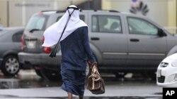 Một người đàn ông trong trang phục truyền thống đi trong mưa ở Dubai, Liên hiệp Các Tiểu vương quốc Ả-rập
