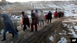 Migrants walk from the Macedonian border into Serbia, near the village of Miratovac, Serbia, in the early morning Saturday, Jan. 23, 2016. Macedonia briefly closed the border to refugees earlier Friday but soon re-opened it. The country is only letting in people from Syria, Iraq and Afghanistan, whom it considers refugees. It rejects all others as economic migrants. (AP Photo/Darko Vojinovic)