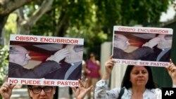Thành viên của phong trào Laicos de Osorno cầm ảnh của Fernando Karadima và Juan Barros, Hồng Y của Osorno, trong một cuộc biểu tình