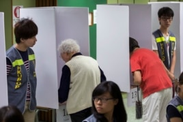 People vote at a polling station during Occupy Central's unofficial referendum on democratic reforms in Hong Kong June 29, 2014.