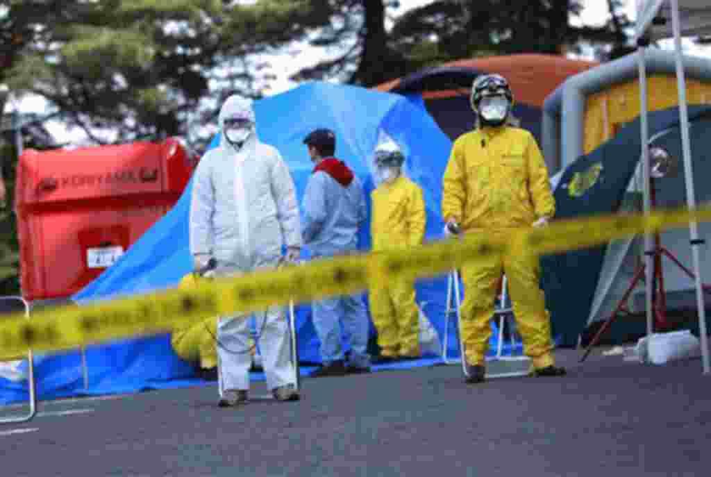 Oficiales del departamento de incendios rodean el área de la central de Fukushima.