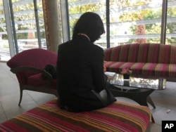FILE - Grace Meng, the wife of missing Interpol President Meng Hongwei, who does not want her face shown, consults her mobile phone in the lobby of a hotel in Lyon, central France, where the police agency is based, Oct. 7, 2018.
