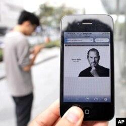 Un homme tenant un iPhone 4 montrant l'avis nécrologique de Jobs