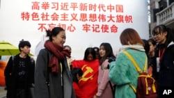 """一群大學生手舉中共黨旗在寫有""""習近平語錄""""的宣傳板前合影。 (2017年11月19日)"""