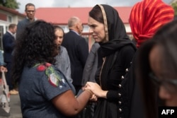 New Zealand Prime Minister Jacinda Ardern speaks with a woman during a visit to the Canterbury Refugee Center in Christchurch, March 16, 2019.
