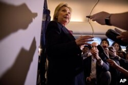 FILE - Democratic presidential candidate Hillary Clinton speaks to members of the media on board her campaign plane as she travels to Tampa, Sept. 6, 2016.