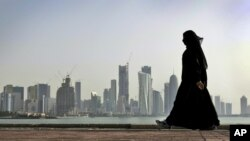 FILE- A woman walks along the waterfront against a backdrop of Doha, Qatar, May 14, 2010. A Dutch woman, imprisoned in Qatar for nearly three months for telling police she'd been raped, reportedly received a one-year suspended prison sentence.