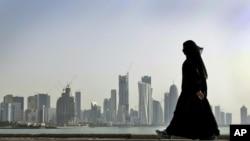 Seorang perempuan Qatar berjalan melintasi panorama keindahan gedung pencakr langit di Doha, Qatar (Foto: dok).