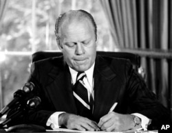 "FILE - Ford signed a document granting Nixon ""a full, free and absolute pardon"" for all ""offenses against the United States"" during the period of his presidency."