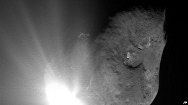 This image provided by NASA shows comet Tempel 1 at the moment of impact with NASA's Deep Impact probe as it smashed into its surface. The probe crashed between the two dark-rimmed craters near the center and bottom of the comet (File Photo - July 4, 2005