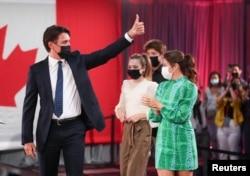 PM Kanada Justin Trudeau, didampingi istrinya Sophie Gregoire dan anak-anak mereka Ella-Grace dan Xavier mengacungkan jempol kepada para pendukungnya, saat berlangsungnya pesta malam pemilihan Liberal di Montreal, Quebec, Kanada, 21 September 2021. (REUTERS)