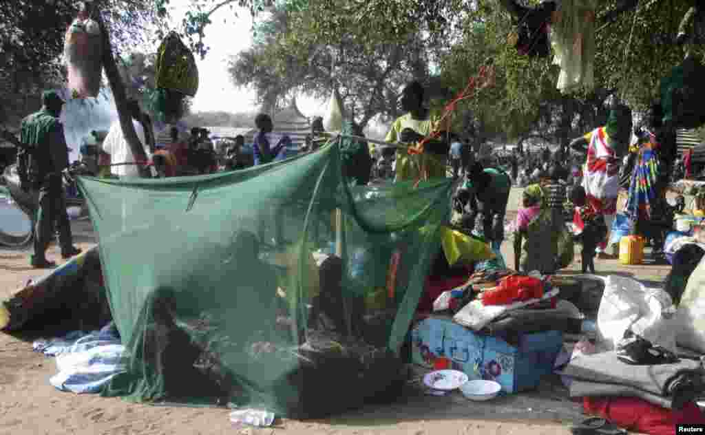 Displaced people gather under a mosquito net tent as they flee from fighting between the South Sudanese army and rebels in Bor town, 180 km (112 miles) northwest from capital Juba December 30, 2013.