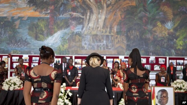 U.S. Secretary of State Hillary Clinton, center, pays her respects after signing the guest book for Ghana's late President John Atta Mill's funeral in Accra, Ghana, August 10, 2012.